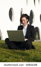 Businesswoman working with a laptop and sitting on the grass