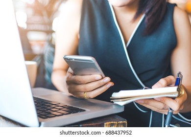 Businesswoman working in office,She holds a cell phone and notepad.