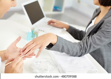 Businesswoman working on computer and her left hand being manicured by beautician