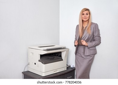 Businesswoman working on a copy machine at the office