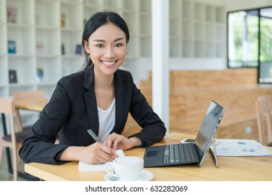 Businesswoman working on desk with laptop computer,Businesswoman using pen for note to do list concept.