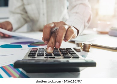 businesswoman working on desk in office and using calculator and laptop with pen for calculate budged money