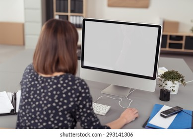 Businesswoman working on a large screen desktop computer while sitting at her desk at the office, view from behind sowing the blank monitor