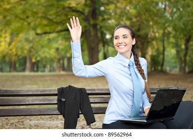 businesswoman working in park and waving hello