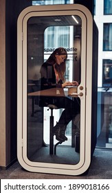 Businesswoman working in phone booth with laptop protect from coronavirus in small closed office