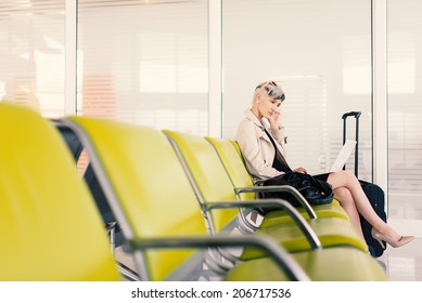 Businesswoman working with portable computer at airport, Paris.