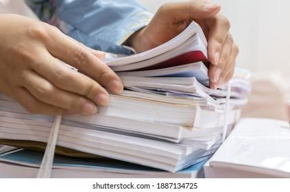 Geschäftsfrau, die in Papierfussstapeln arbeitet, um Informationen über unfertige Dokumente über das Sammelaudit-Formular bei der Schreibtischabteilung zu durchsuchen und den Finanzdoc bei Arbeitsbelastung zu untersuchen