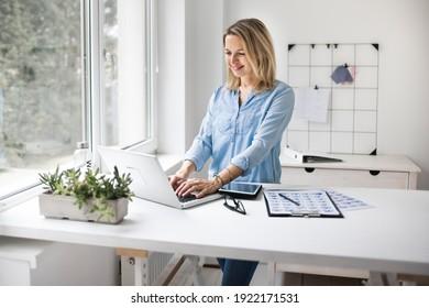 Geschäftsfrau, die an einem ständigen Schreibtisch arbeitet