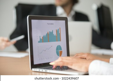 Businesswoman working with statistical report at team meeting analyzing marketing result graphs charts online on laptop screen, business software for project data analysis concept, close up view