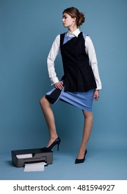 Businesswoman in working suit standing with her feet on printer in studio with blue background