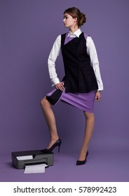 Businesswoman in working suit standing with her feet on printer in studio with purple background