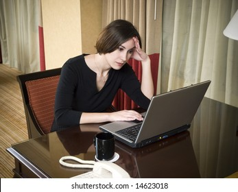 A businesswoman works late into the night on a frustrating problem using her laptop in her hotel room while on a business trip.