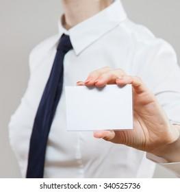 Businesswoman in wormalwear showing business card, neutral background