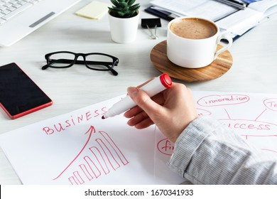 Businesswoman write business plan idea with strategy and chart growth concept. Business planning concept. Office workplace.