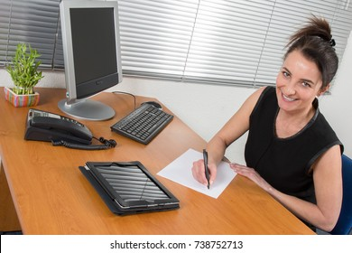 a businesswoman write in paper sitting on office desk with smile
