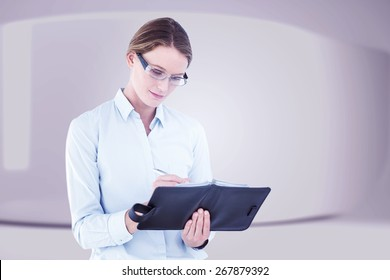 Businesswoman writing in her diary against white abstract room