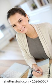 Businesswoman writing on agenda in office