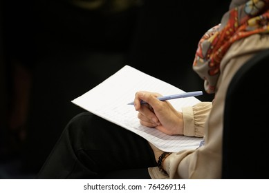 Businesswoman writing on notepad during a meeting, closeup