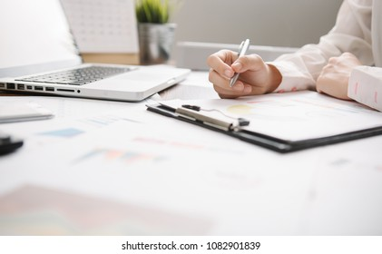 Businesswoman Writing with pen on business document