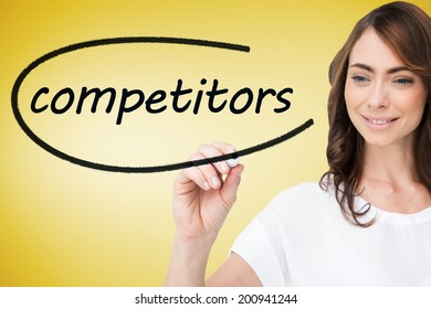 Businesswoman writing the word competitors against yellow vignette