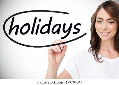Businesswoman writing the word holidays against white background with vignette