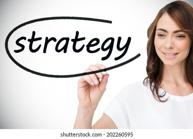Businesswoman writing the word strategy against white background with vignette