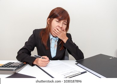 Businesswoman yawn or feel sleepy while working at office after having launch.