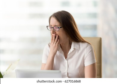 Businesswoman yawning while sitting in office. Woman feeling lack of sleep during working day. Female employee bored monotonous routine work. Sleepy girl struggles with drowsiness at the workplace