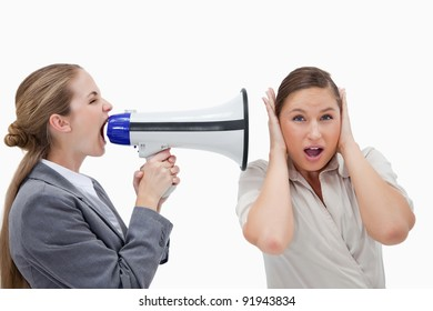 Businesswoman yelling at her coworker through a megaphone against a white background