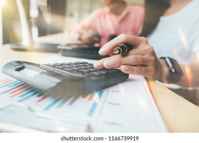 businesswomanhand working with finances about cost and calculator and laptop with tablet on wood desk at office warm colours sun light