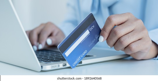 The businesswoman's hand is holding a credit card and using a laptop for online shopping and internet payment.