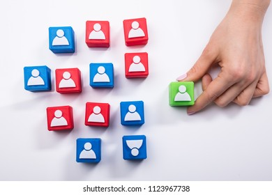 Businesswoman's Hand Holding Green Cubic Block Near Team Of Red And Green Blocks