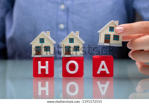 Businesswoman's Hand Placing House Models On Red HOA Cubic Blocks Over Desk