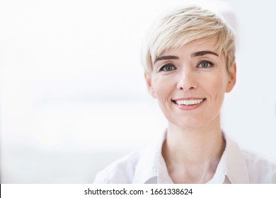 Businesswoman's Portrait. Cheerful Female Entrepreneur Smiling At Camera Posing Near Window Indoor. Free Space, Selective Focus