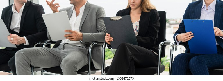 Businesswomen and businessmen holding resume CV folder while waiting on chairs in office for job interview. Corporate business and human resources concept.