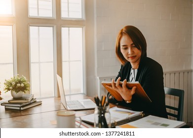 Businesswomen checklist on board and working on office desk.