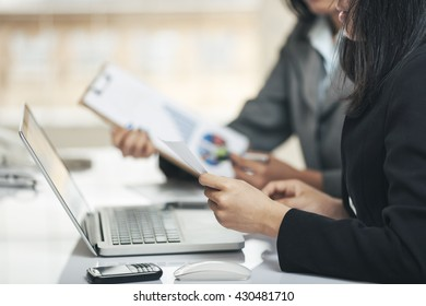 businesswomen comparing the graphical documents with the docs on the laptop