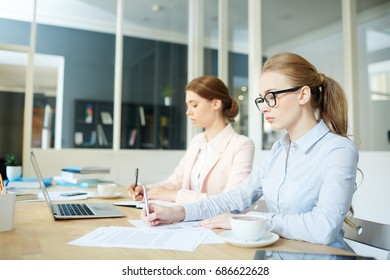 Businesswomen concentrating on paperwork or financial analysis