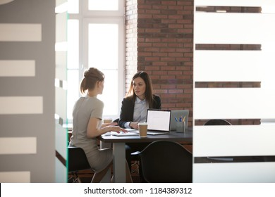 Businesswomen discussing project results and planning work in meeting room, female marketing or sales executives talking in office, serious women colleagues sharing ideas about new corporate strategy