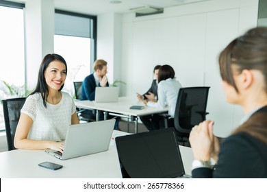 Businesswomen exchanging thoughts in a nice office environment while working on a laptop