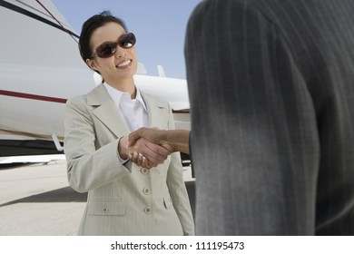 Businesswomen giving each other a handshake at the airport