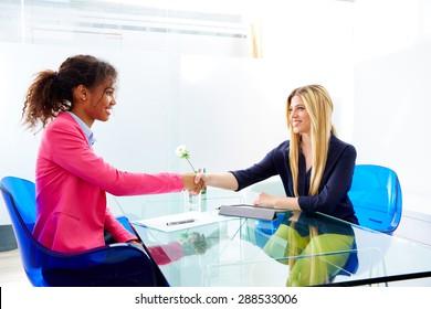 businesswomen interview handshake multi ethnic africand and blond sitting at office