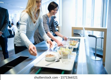 Businesswomen with lunch trays in work cafeteria