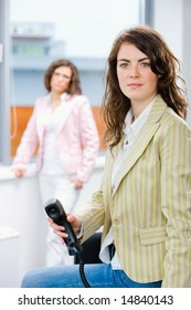 Businesswomen at office, business woman calling on phone.