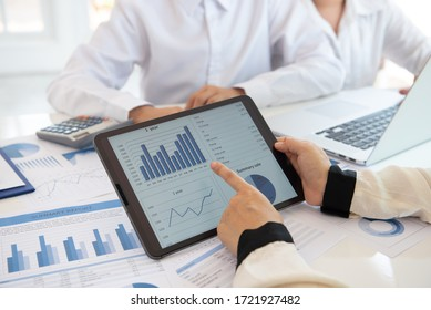businesswomen pointing business financial report on digital tablet during discussion at meeting of corporate showing the results of their successful teamwork.