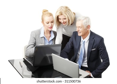 Businesswomen and senior businessman using laptop while working together on presentation. Group of business people sitting around desk and consulting. Teamwork.  Isolated on white background.