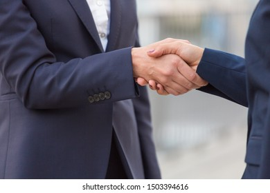 Businesswomen shaking hands. Close-up partial view of professional female colleagues shaking hand soutdoor. Business handshake concept