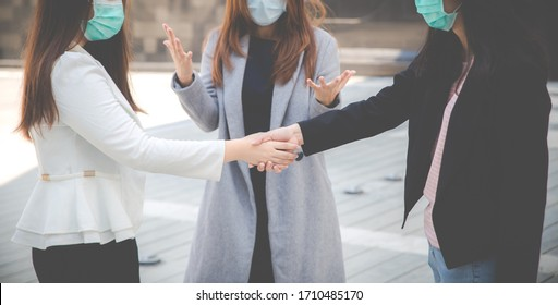 Businesswomen shaking hands with people in the background. Two confident businesswomen shaking hands and wearing face protection in prevention for coronavirus. Business concepts, Air pollution.
