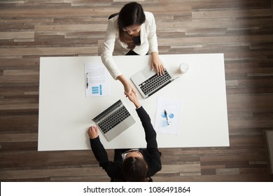 Businesswomen shaking hands sitting at office desk making successful partnership deal, women in business handshaking above work table thanking for help or successful teamwork, top view from above