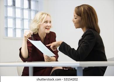 Geschäftsfrauen, die am Büroschreibtisch sitzen und über Papierkram gehen, die nach und nach hinweisen und lächeln.